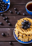 Wafers with chocolate sauce and blueberry. On a dark wooden background Stock Photo