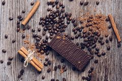 Wafers in chocolate on a wooden table with coffee beans and cocoa powder. View from above. Royalty Free Stock Photo
