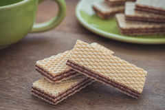 Wafers with chocolate on wooden table and coffee cup Royalty Free Stock Photography