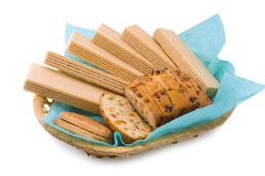 Wafers, a fruitcake and cookies. In a wattled basket on a white background Royalty Free Stock Images