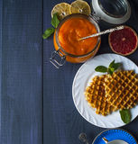 Wafers on white plate with a jar of persimmon jam Royalty Free Stock Photo