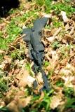 Waffe, die in einem Gras liegt stockbilder