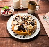 Waffel with some fruit and coffee. Waffel with bananas, blueberries and coffee on a table royalty free stock images