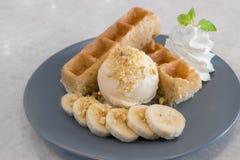 Waffeln mit dem Vanilleeis, Banana split u. gesalzener Karamellsoße, dienend auf der grauen Platte, essfertig stockfoto
