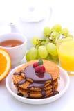 Waffeln mit Schokolade und Himbeeren, Trauben, Tee und Orangensaft stockbilder