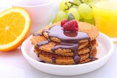 Waffeln mit Schokolade und Himbeeren, Trauben, Tee und Orangensaft stockfotografie