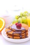 Waffeln mit Schokolade und Himbeeren, Trauben, Tee und Orangensaft stockfotos