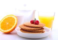 Waffeln mit Schokolade und Himbeeren, Trauben, Tee und Orangensaft lizenzfreies stockbild