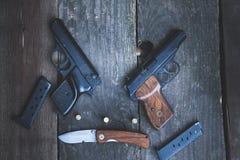 Waffen auf dem Hintergrund eines Holztischs Stockbild