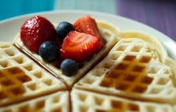 Waffle avec des fraises, des myrtilles et le sirop d'un plat Image stock