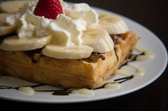 Waffle with banana, whipped cream and strawberry. Waffle with banana, whipped cream, nutella and strawberry on a white plate and black background royalty free stock images
