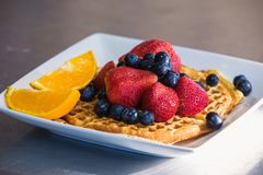 Waffle with berries and orange royalty free stock image