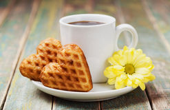 Waffle biscuits in shape of heart with cup of coffee and flower on rustic background for Valentines day Stock Image