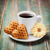 Waffle biscuits in shape of heart with cup of coffee and flower on vintage background Royalty Free Stock Image