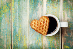 Waffle biscuits in shape of heart with cup of coffee on wooden background for Valentines day