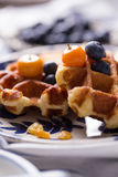 Waffle. Blueberry apple waffle with honey set on a dish decorated with fresh blueberry, apple and almond Stock Images