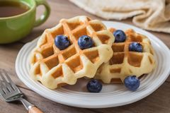 Waffle with blueberry on plate and cup of tea Royalty Free Stock Photo