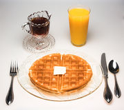 Waffle for Breakfast. A waffle breakfast with melting butter, syrup and a glass of orange juice stock photos