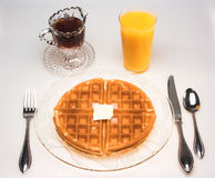 Waffle for Breakfast (high perspective). A waffle breakfast with melting butter, syrup and a glass of orange juice stock photography