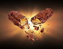 Waffle chocolate bar with nuts broken into two parts in the dark.  stock photo