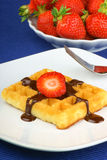 Waffle with chocolate and strawberry. Waffle with chocolate sauce and strawberry slices on a white porcelain dish over a blue tablecloth. In the background some stock image