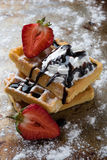 Waffle with chocolate syrup. On a sugary steel plate Stock Photos