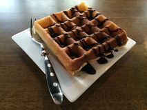 Waffle with chocolate syrup. Waffle with chocolate syrup on white dish royalty free stock images