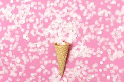 Waffle cone with bouquet of round confetti on pastel pink background. Festive holiday background, concept of party, birthday. Creative holiday concept minimal stock images