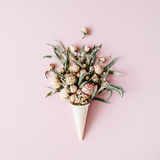 Waffle cone with roses bouquet on pink background stock photography