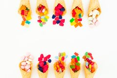 Waffle cones with assorted bright candy on white background. Flat lay, top view. Waffle cones with assorted bright candy on white background. Flat lay stock image