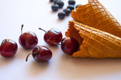 Waffle cones with blueberries and cherries royalty free stock photo