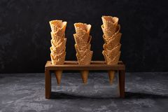 Waffle cones in ice cream cone stand on a on black background. Three nested ice cream waffle cones waiting to be filled with ice cream on a black background royalty free stock photo
