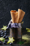Waffle cones for ice cream. Empty waffle cones for ice cream in old tin can with paper and carambola, mint leaves, blueberries and matcha powder over black Royalty Free Stock Photos