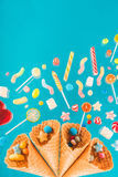 Waffle cones and mix of various sweets on blue background Royalty Free Stock Images