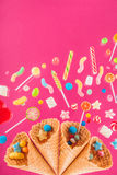 Waffle cones and mix of various sweets on pink background Stock Image