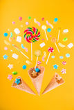 Waffle cones and mix of various sweets on yellow background Stock Images