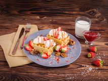 Waffle dessert, a glass of milk and a fork with a knife on a napkin. On a wooden table. Royalty Free Stock Images