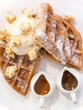 Waffle dressed with pop corn, ice cream and chocolate and caramel sauces stock images