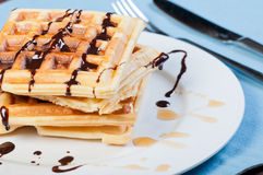 Waffle with a drizzle of chocolate and caramel syrup Royalty Free Stock Photos