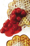 Waffle filled with cream and hot cherries, elevated view, close-up Royalty Free Stock Image
