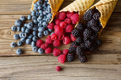 Waffle with fresh berries. Berries. Raspberries, blackberries, blueberries in waffle cones on a gray abstract background. Stock Photo