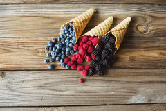 Waffle with fresh berries. Berries. Raspberries, blackberries, blueberries in waffle cones on a gray abstract background. Copyspace. Healthy food concept stock photo