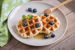 Waffle with fresh blueberry and honey on plate Royalty Free Stock Photo