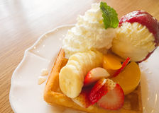 Waffle with fruits on wooden table Stock Photos