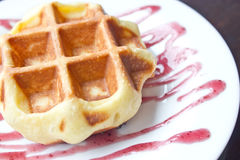 Waffle with grape sauce. Royalty Free Stock Photography