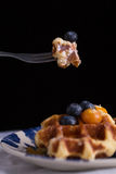 Waffle and honey. Blueberry waffle set in a nice dish and a fork cut in piece on black background copy space Stock Photo