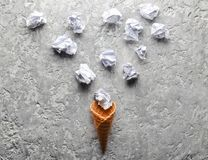 Waffle horn and balls of crumpled paper on a gray concrete surface. Creative layout, minimal trend. Waffle horn and balls of crumpled paper on a gray concrete royalty free stock photos