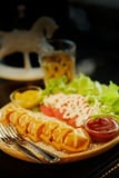 Waffle hot dog stick set with salad and hot tea on table Royalty Free Stock Image