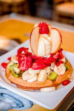 Waffle with ice cream and fruits on a plate. In a dinner. Vertical Royalty Free Stock Photos