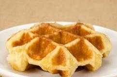 Waffle. Image of waffle in white ceramic dish on brown sack background stock photos